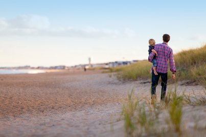 Father walking with his child on a beach in Ohio.  The father is happy because of term life insurance quote he received.